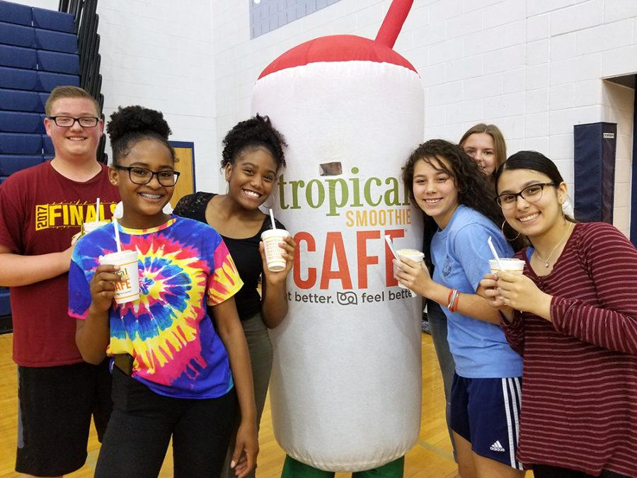A Tropical Smoothie employee poses with students after they received their free drinks.