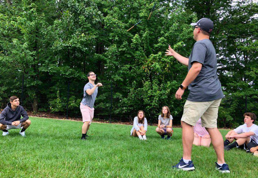 Ely and band director Daniel Upton toss wooden rods to each other as part of a communication activity.