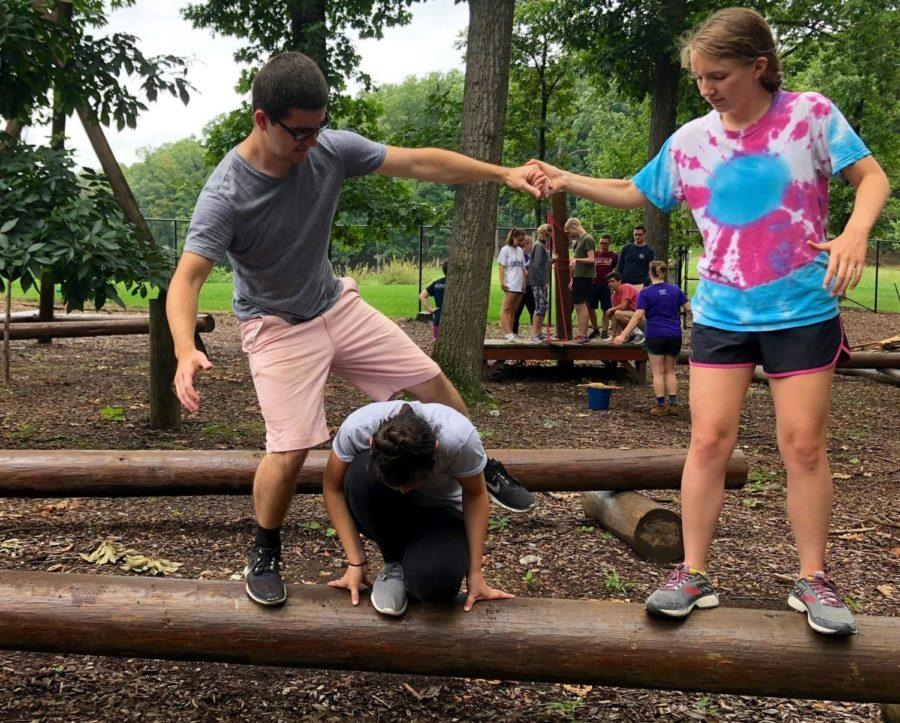 Junior Carly Corso assists senior Andrew Ely as he crosses over Carper as part of a teambuilding activity.