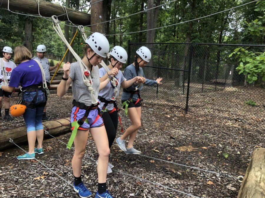 Junior+Spencer+Spears+and+seniors+Precious+Carper+and+Irene+Liu+work+with+each+other+to+stay+balanced+as+they+learn+the+basics+of+the+ropes+course.