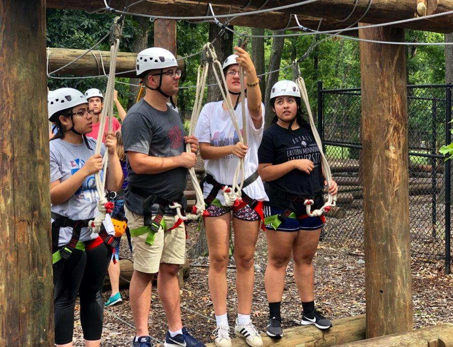 Senior Emily Chirinos, band directior Daniel Upton and juniors Ruby North-Sandel and Wendy Santiago practice doing safety checks with each other before going on the ropes course.