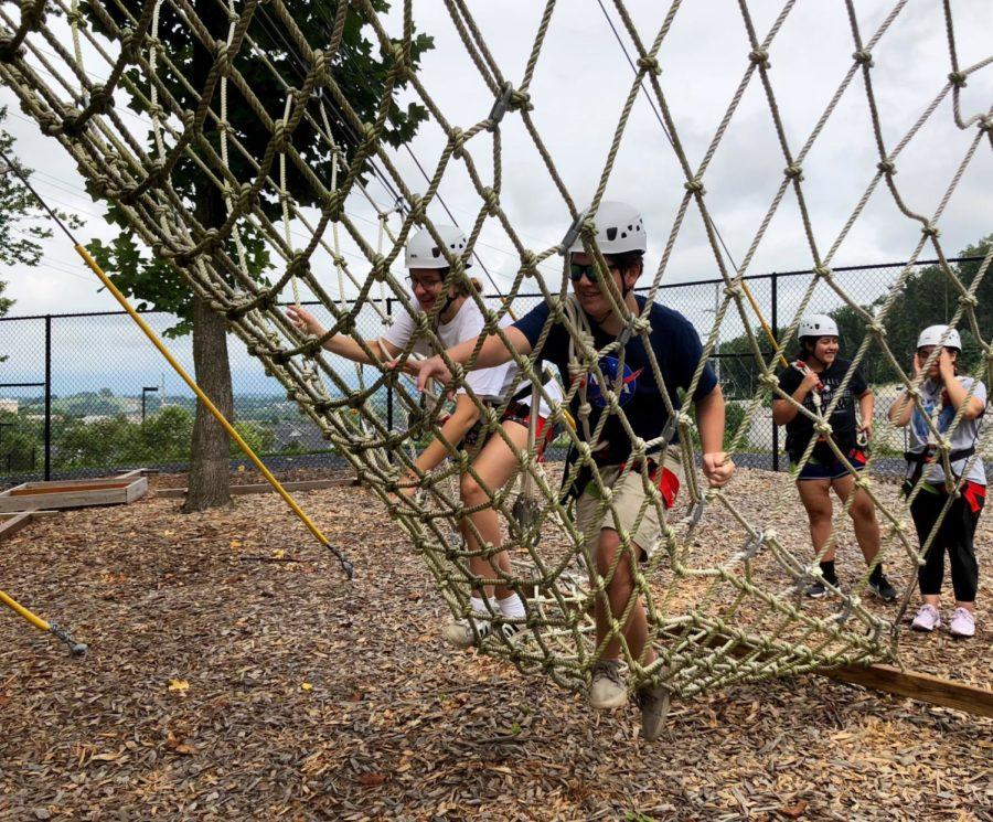 Juniors Ruby North-Sandel and Leif McCoy climb the cargo net in order to begin the ropes course.