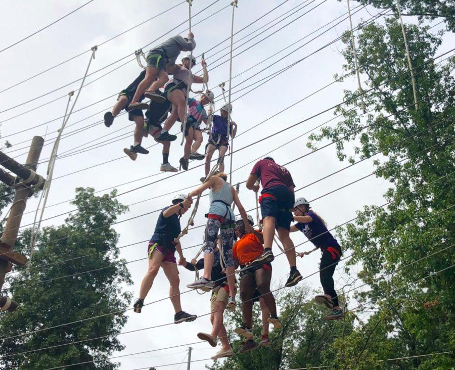 Two separate groups of participants cross the wires of the ropes course on different levels.
