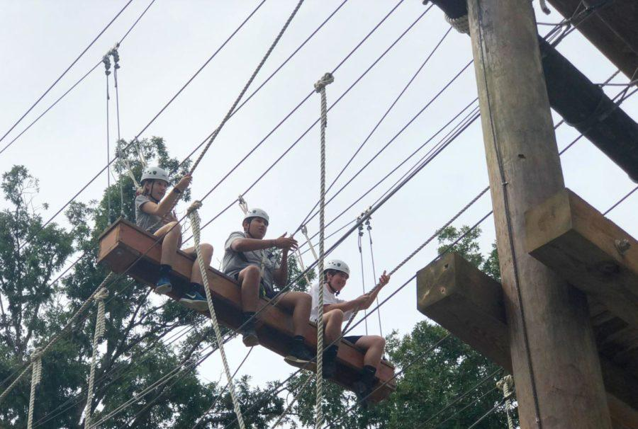 Junior Spencer Spears, senior Ronal Gomez and junior Jack Hotchkiss pull themselves across a section of the ropes course.