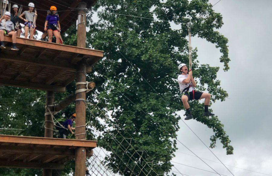 Junior Jack Hotchkiss rides the zipline as the final part of the ropes course.