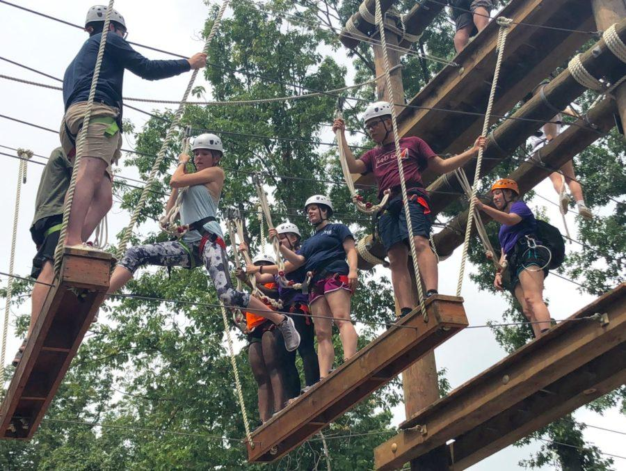 Obenschain jumps across the gap between two wooden steps on the ropes course.