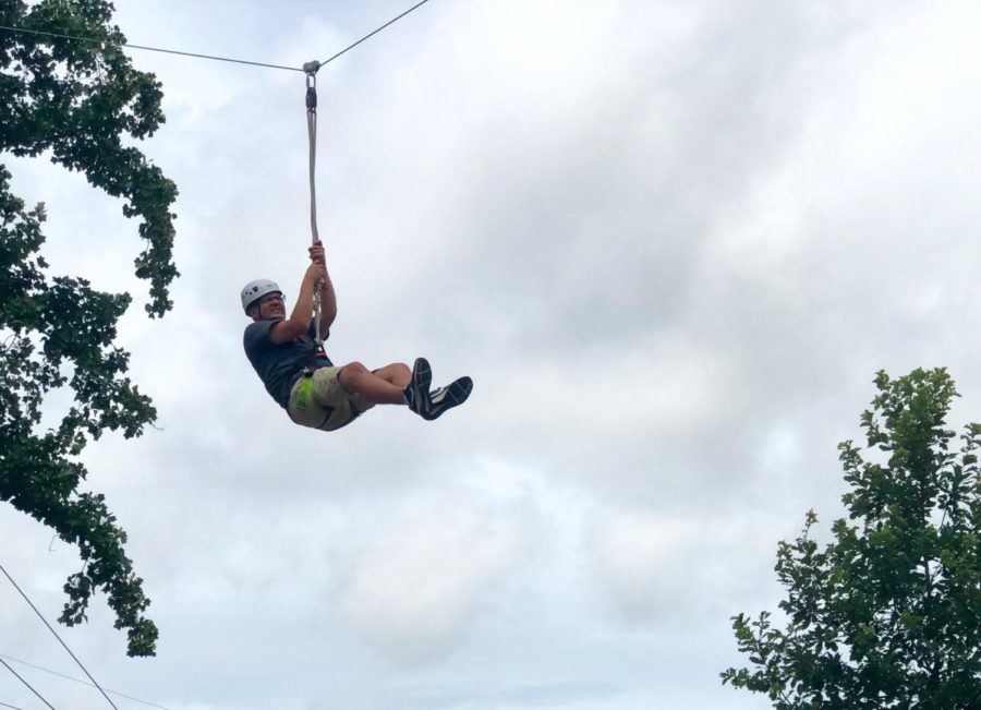 Band director Daniel Upton rides the zipline to conclude the course.