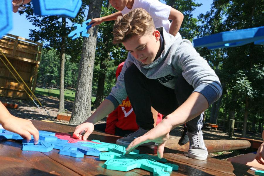 Sophomore Dmitriy Kukharchuck arranges lizard-shaped puzzle pieces. He and his other 11 group members had to complete it without verbally communicating.