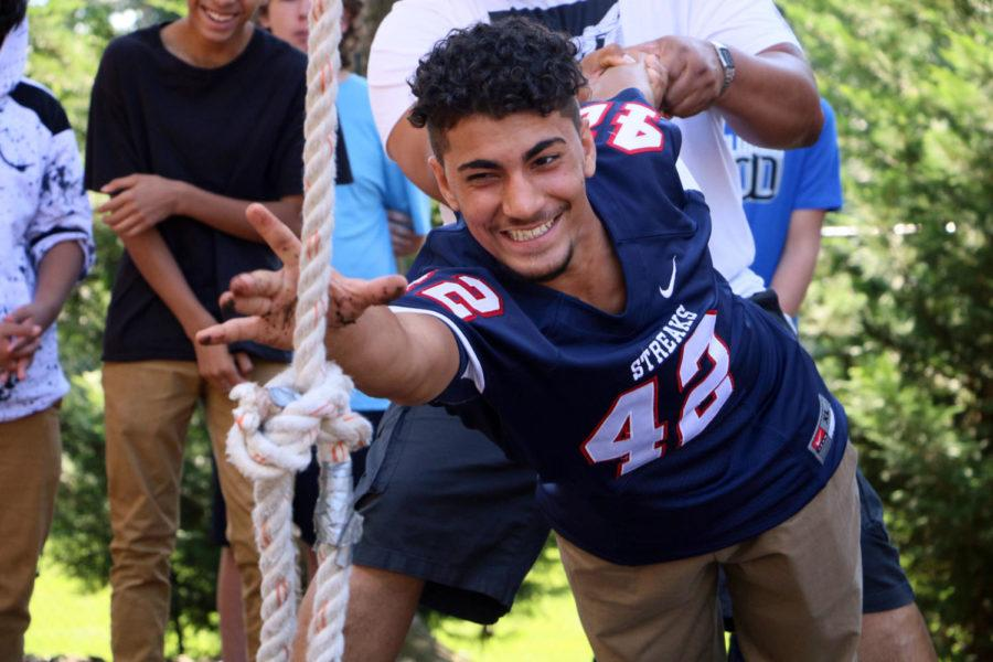 Sophomore+Nyaz+Mamund%2C+supported+by+a+member+of+his+group%2C+reaches+over+an+obstacle+for+a+rope.+Over+40+freshmen+and+sophomore+in+the+Summit+Academy+visited+the+JMU+ropes+course+to+take+part+in+a+variety+of+team+building+activities.+