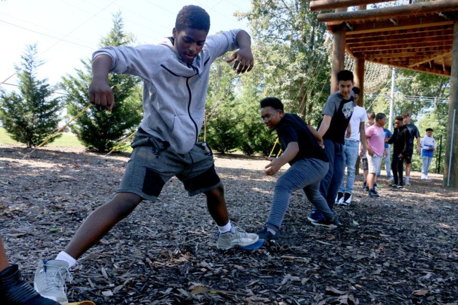 Students in the Summit Academy reach to make it the the other side of the course without stepping on the ground.