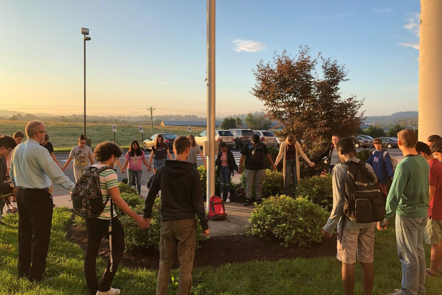 Students at the See You At The Pole event gather around the flagpole in a circle and pray.