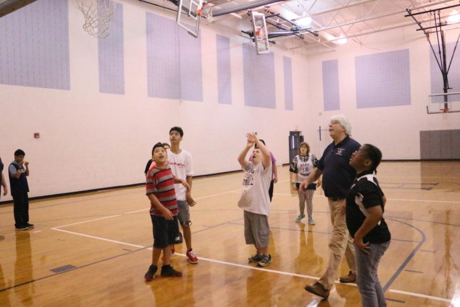 Teacher Walt Williamson coaches the team as Donnie Winton takes a shot.