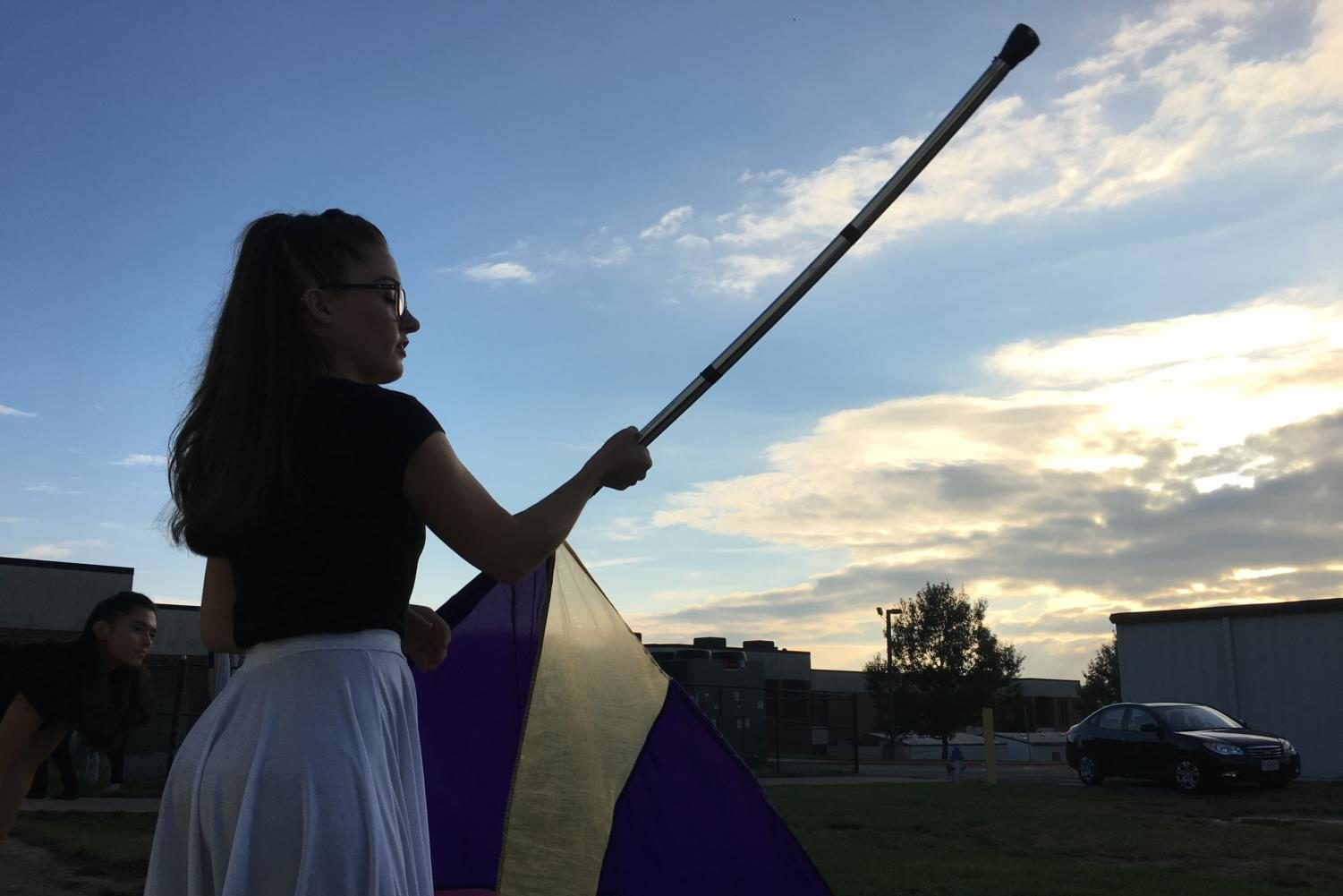 A color guard member twirls a flag before performing at the City County Showcase at Broadway High School.