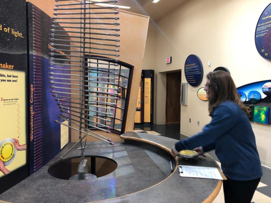 Sophomore Stella Alexiou uses metal rods and a wheel to observe changes in wavelength and how to manipulate a radio wave.