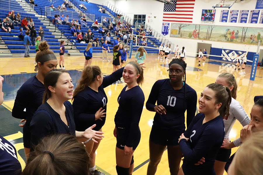 The varsity volleyball team has a game plan discussion while the Spotswood blazers are warming up.