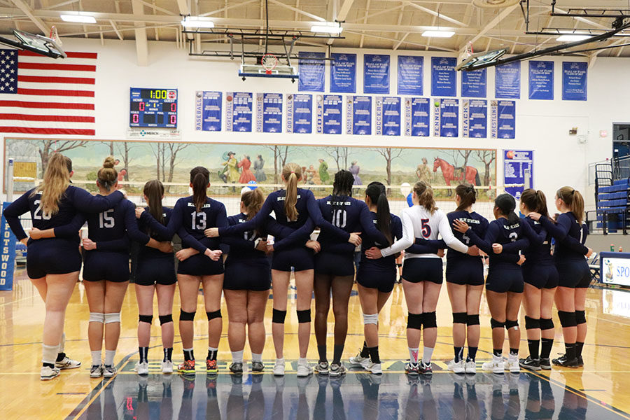 The varsity volleyball team links arms for the national anthem before their match against Spotswood High school on the 18th of October.