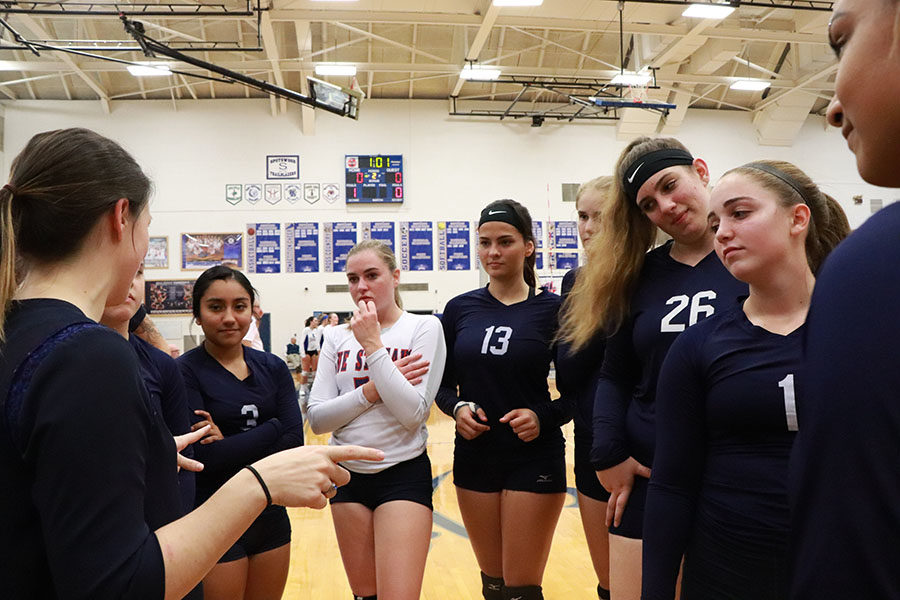 Coach Hannah Bowman talks tactics with the varsity volleyball team at the end of the first set.