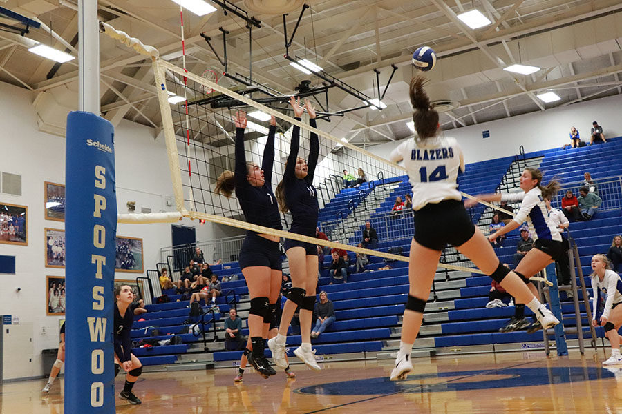 Freshman Maya Waid and sophomore Amelia Mitchell block an oncoming hit from the Spotswood Blazers in the third set.