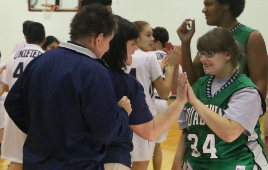Assistant Coach Lisa Long gives a Broadway player high five after the game against Broadway. The Gobblers won with the final score 39-27.