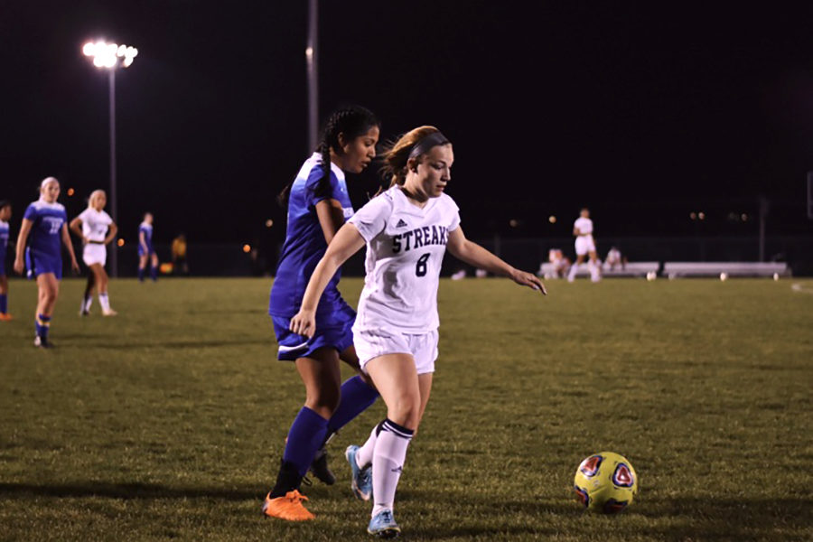 Senior Mikaela OFallon dribbles the ball away from a defender. OFallon tore her ACL in October 2015 and has recovered since.