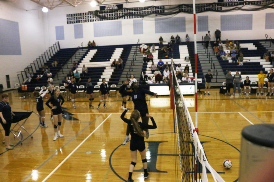 Junior Atilia Thomas hits the ball in warm ups before the game.