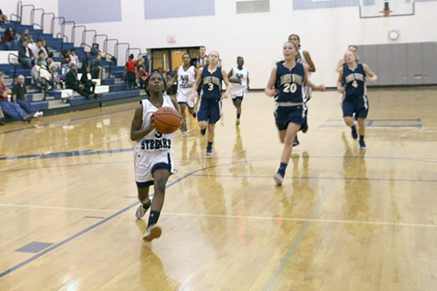 Sophomore Calayiah Stuart runs to the opposite end in an attempt to score a two pointer for the girls basketball team as they face off against James Wood.