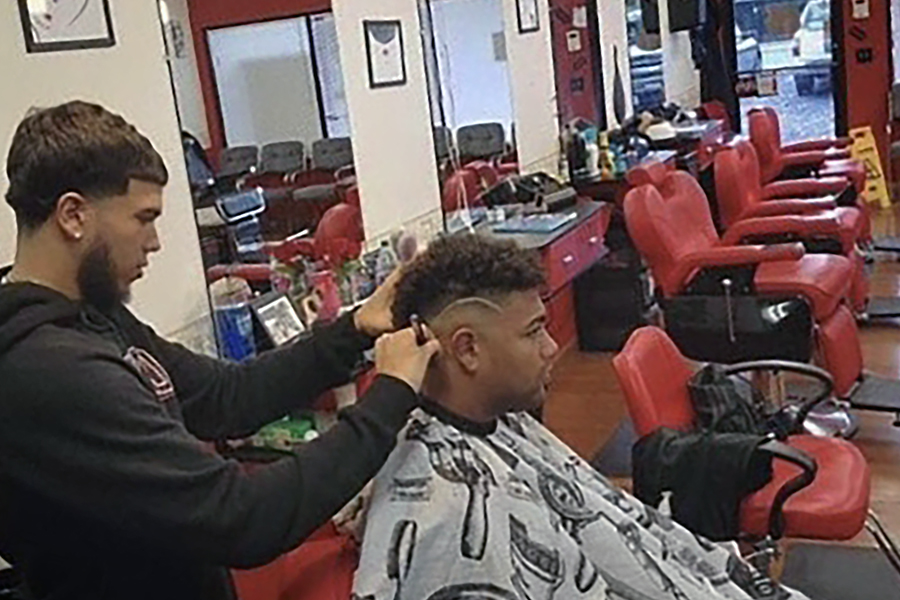 Delgado gives senior Jungle Rodriguez a haircut at Corte Latino, where Delgado currently works.