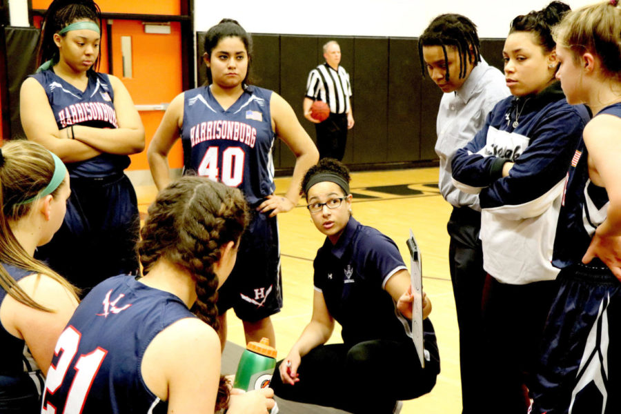 Coach Allysia Rohlehr talks to the JV girls basketball team during a time out in the second quarter of a game at Charlottesville.