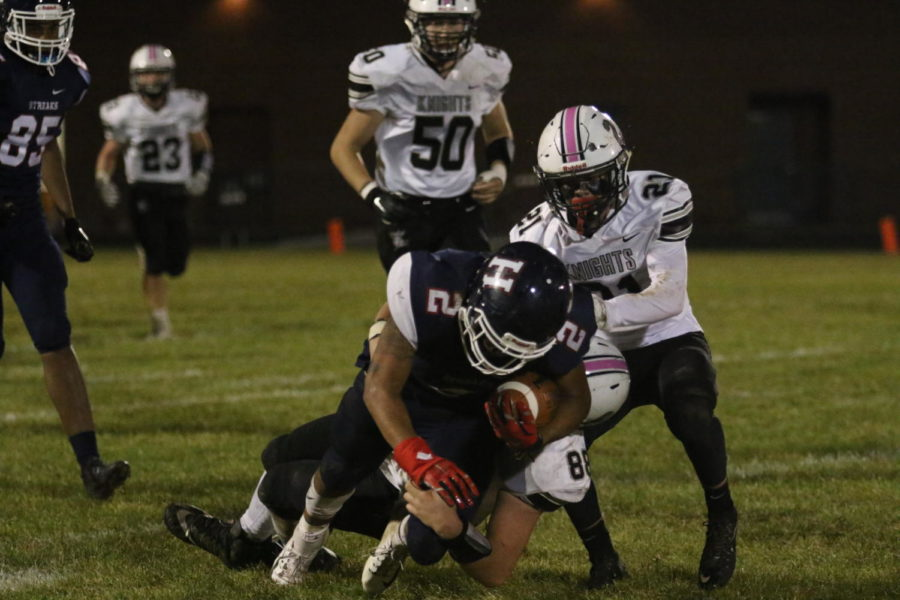 Senior Marcus Robinson-Jenkins falls forward to pick up extra yardage as he is tackled from behind.