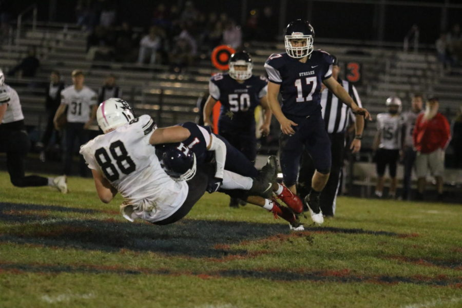 Junior Austin White bashes a TA player to the ground at midfield.