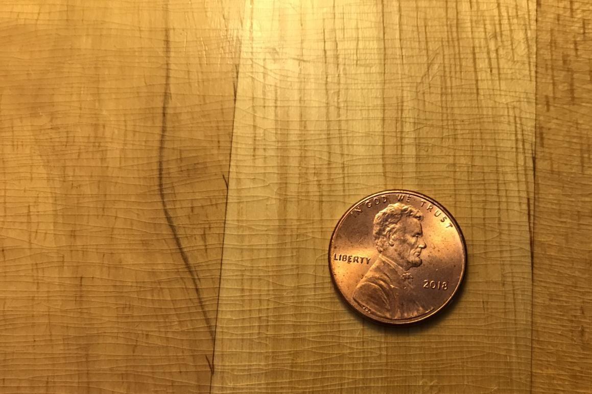 A penny sits uselessly on Sid's desk.