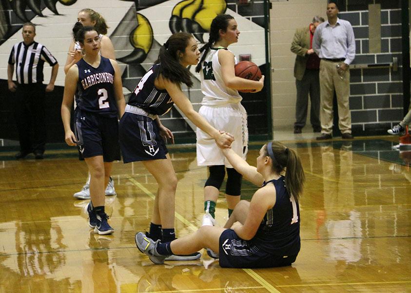 Freshman Mariah Cain helps up Maya Waid after a foul is called.