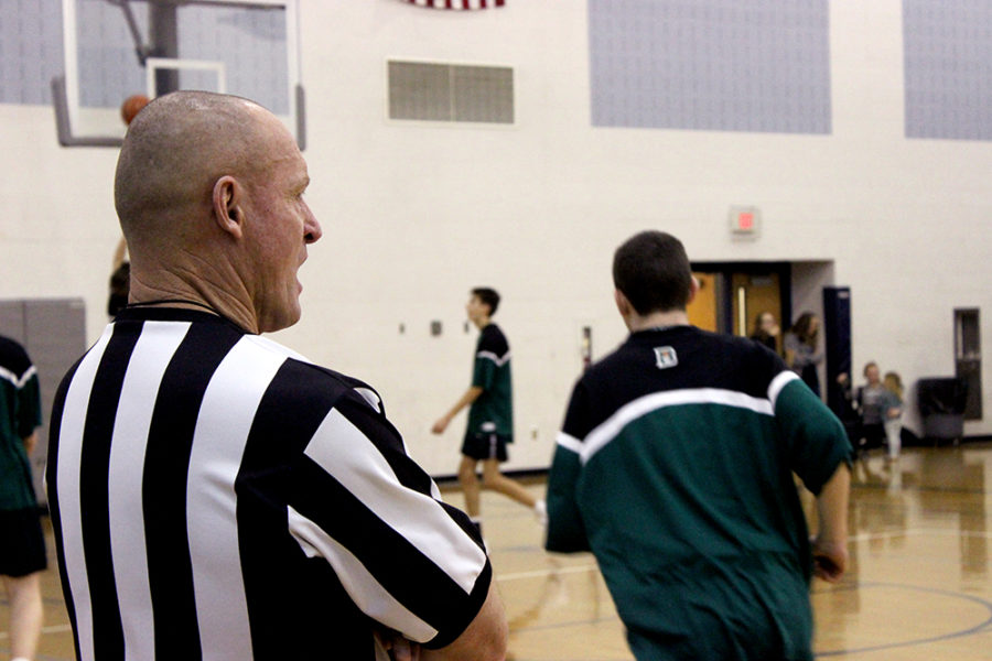 Referee looks on as players warm up for their match.