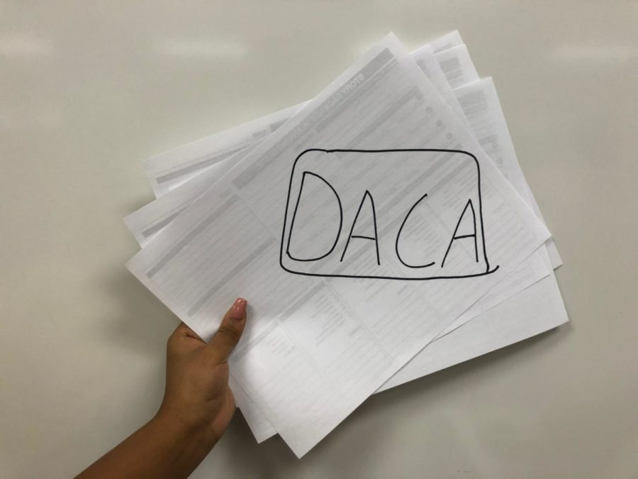 Papers are held with 'DACA' written on them.