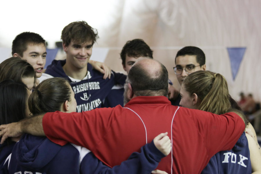 Swim coach Richard Morrell huddles up with the senior swimmers after recognizing them during the meet.