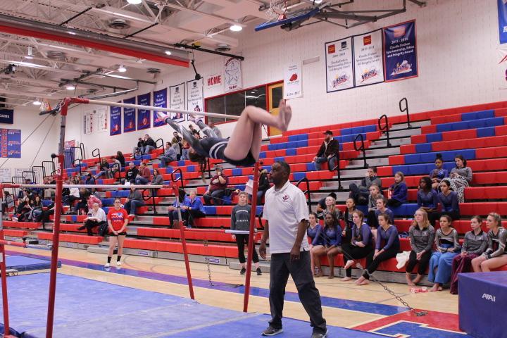 Harrisonburg+High+School+gymnastics+coach+Michael+King+spots+Turner+Ashby+High+School+gymnast+Gracie+Armstrong+on+bars.