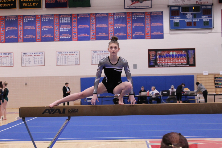 Sophomore+Laney+from+Turner+Ashby+High+School+does+a+wolf+turn+on+beam.+