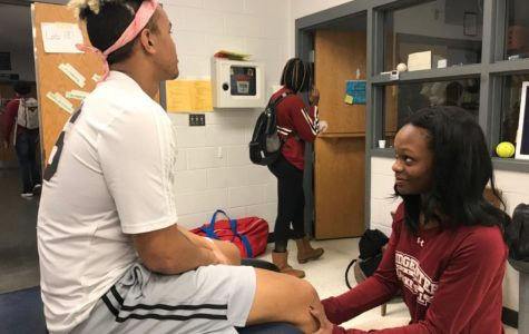 Bridgewater College student and trainer intern at HHS athletics, Tyler Pinder, works with senior Micah Yutzy during indoor track season. After Pinder graduates college, she hopes to start working on her own with high school athletes and then work her way up to the college level.