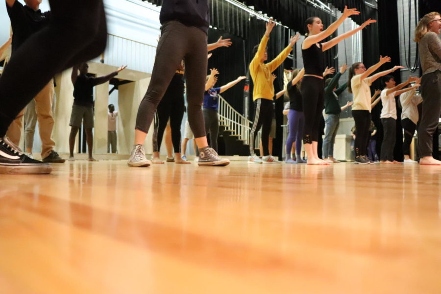 The cast practices the choreography for an iconic scene in the musical.
