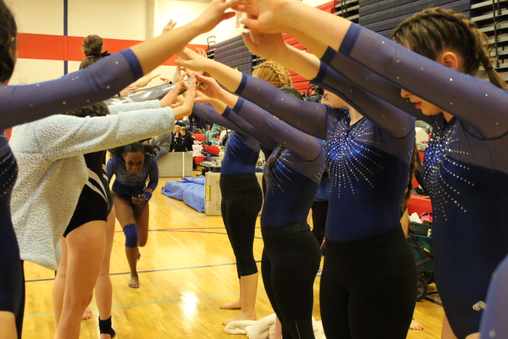 Sophomore+Dorothy+Yates+goes+through+the+gymnast+tunnel+after+competing+on+vault.+She+received+a+hug+from+Sophomore+Chloe+Nichols+at+the+end.