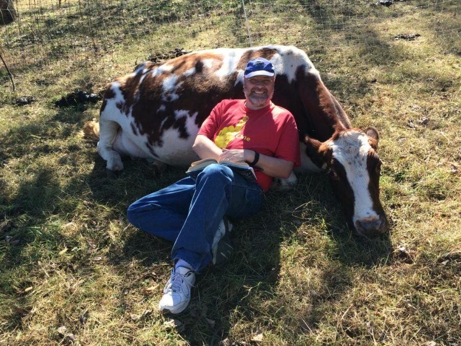 Social studies teacher Mark Tueting relaxes with one of his cows back at his farm. Tueting runs his own farm in Batesville, Virginia, where he lives a different lifestyle when he isnt creating tests or grading worksheets in a classroom setting.