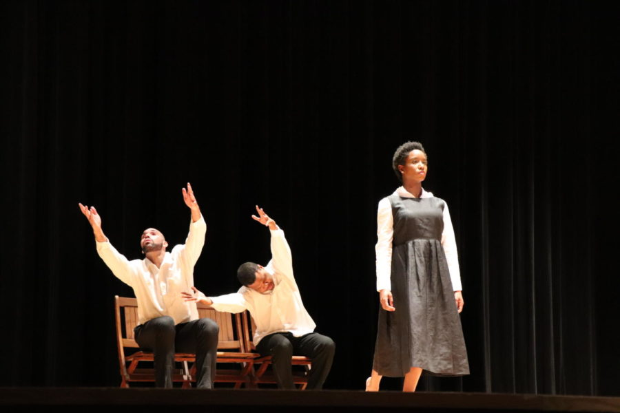 Two dancers sit on a bench while Christian walks forward.