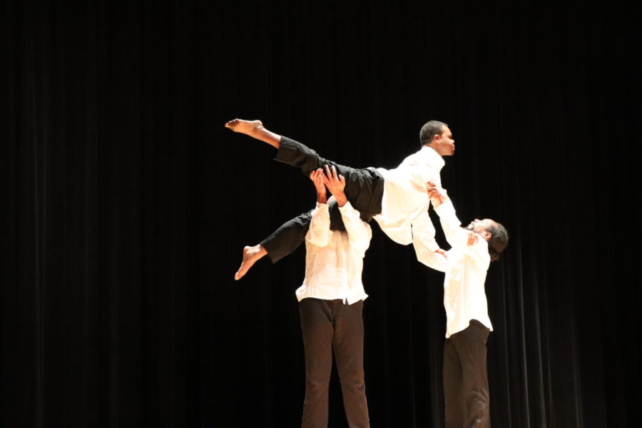 Henries and Walker lift up Riddick in the second segment of the performance.