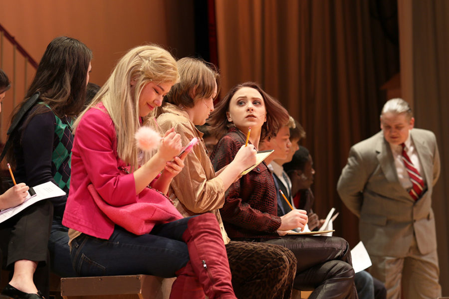 Senior Julia Inouye (left), playing Elle Woods, takes notes in her first law class. In this scene, Inouye had to act oblivious to the difference between her and the classmates around her.