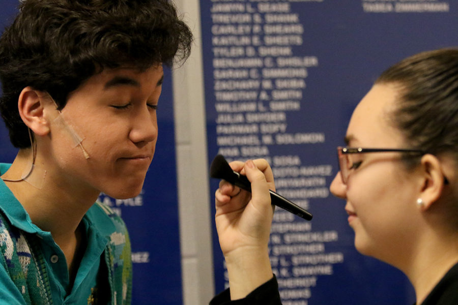 Junior Lizzy Burzumato does sophomore Stanley Inouyes makeup before the show.