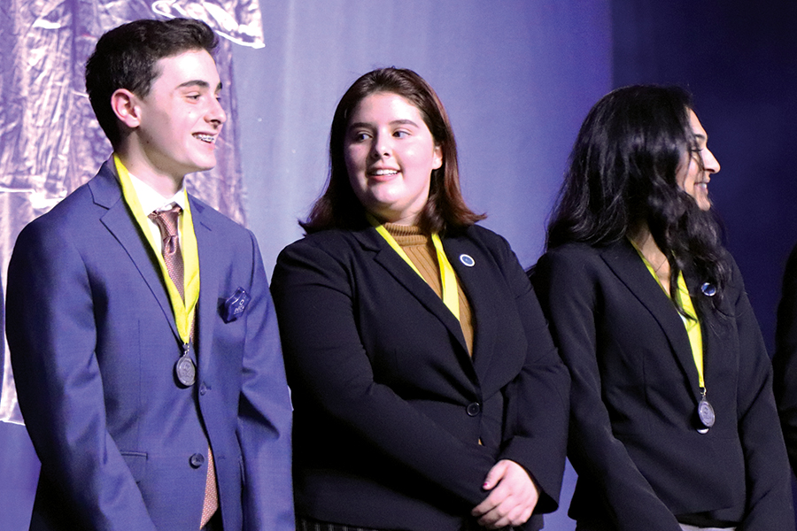 Junior Ann Diaz-Exposito (center) receives her medal for an outstanding test score. Diaz-Exposito is one of four DECA members who qualified for ICDC.