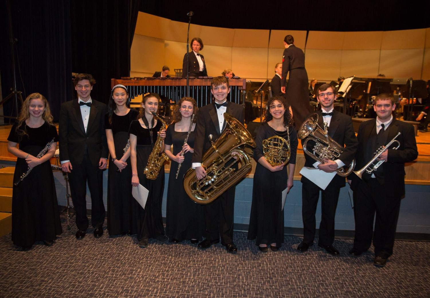 Nine+students+smile+in+excitement+after+performing+with+the+Navy+Band.+