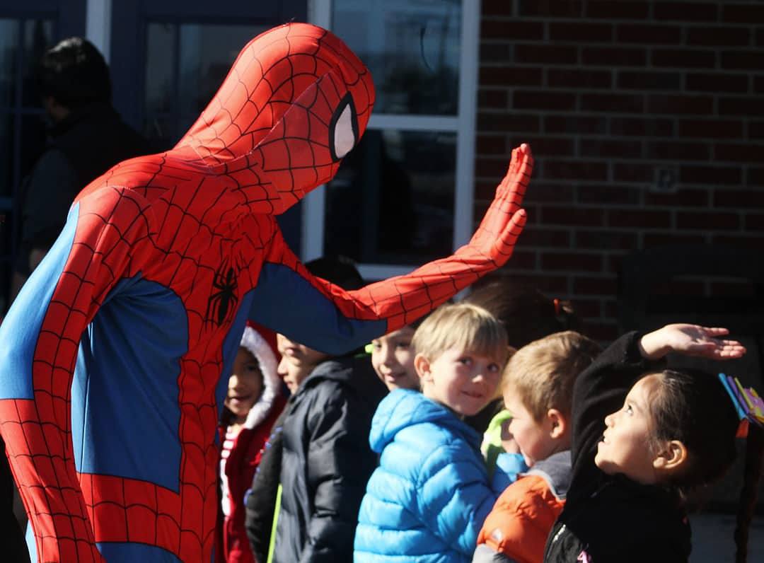 Junior+Declan+Leach+as+Spider-Man+greets+the+line+of+elementary+students+with+a+high-five.