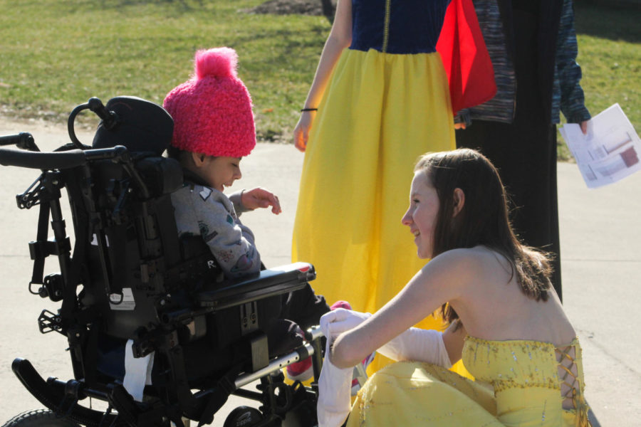 Junior Spencer Spears as Belle discusses her gloves to a kid.