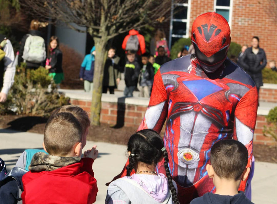 Senior Stefan Aguirre as a power ranger welcomes the elementary students with a low-five.
